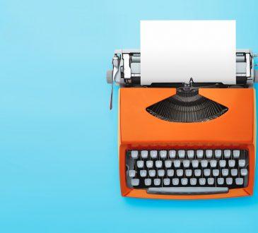 orange typewriter on blue background