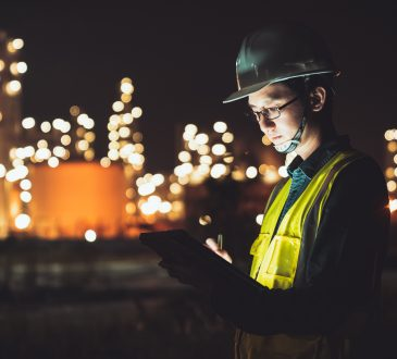 Male engineer using digital tablet working late night shift at petroleum oil refinery in industrial estate.