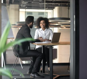 man and woman having meeting in office