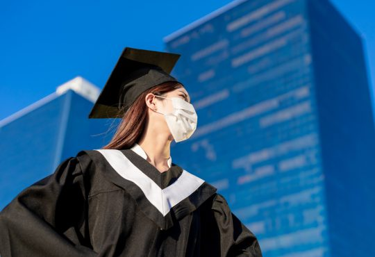 female student wearing graduation gown and mask