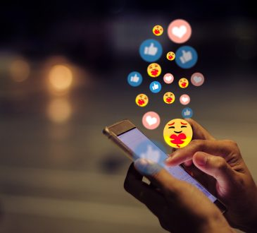 Young woman using smart phone with emojis above