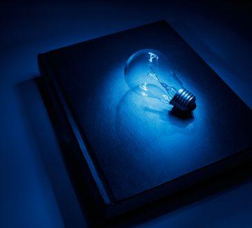 lightbulb on top of book in blue lighting