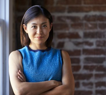 businesswoman standing against brick wall in office
