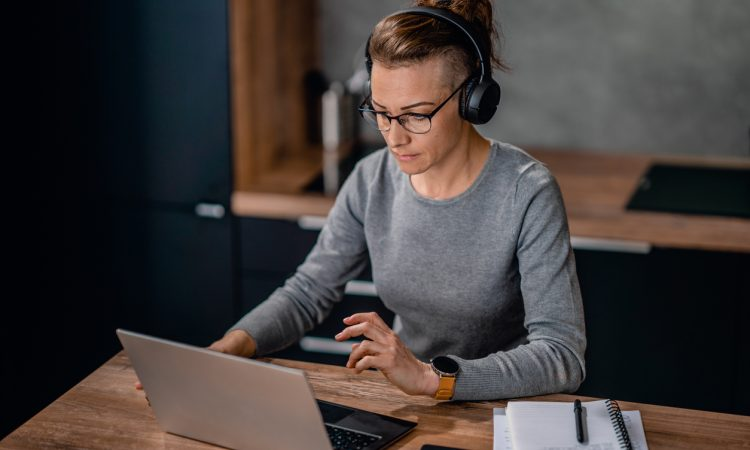Focused woman wearing headphones, watching a webinar and writing notes.
