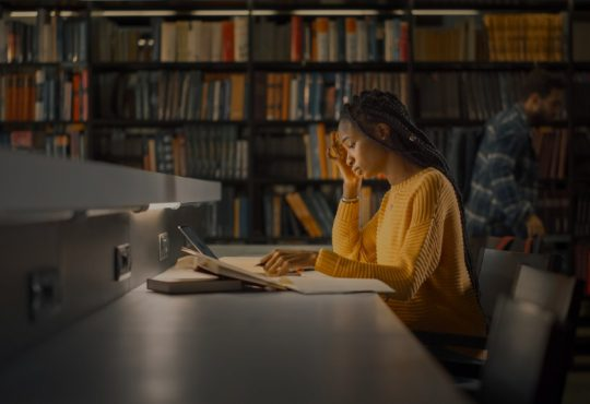 black woman student working in library