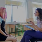 female student and female school counsellor talking in classroom