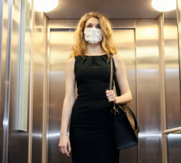 woman wearing business dress and mask in elevator