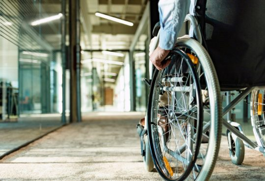 person using wheelchair in building hallway
