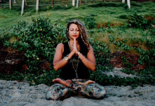 woman sitting in meditative pose outside