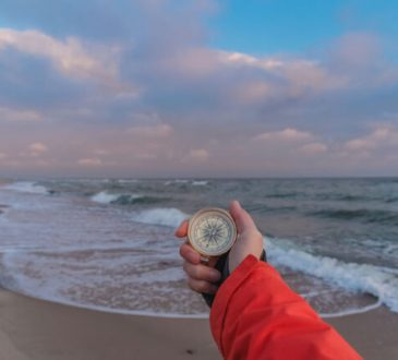 First-person view of a female hand with a compass on a background of ocean