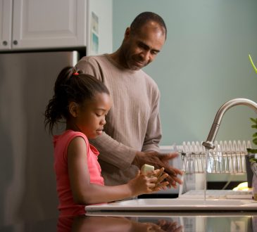 father and daughter washing dishes together