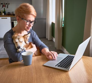 woman hugs her dog while working at home at the laptop.