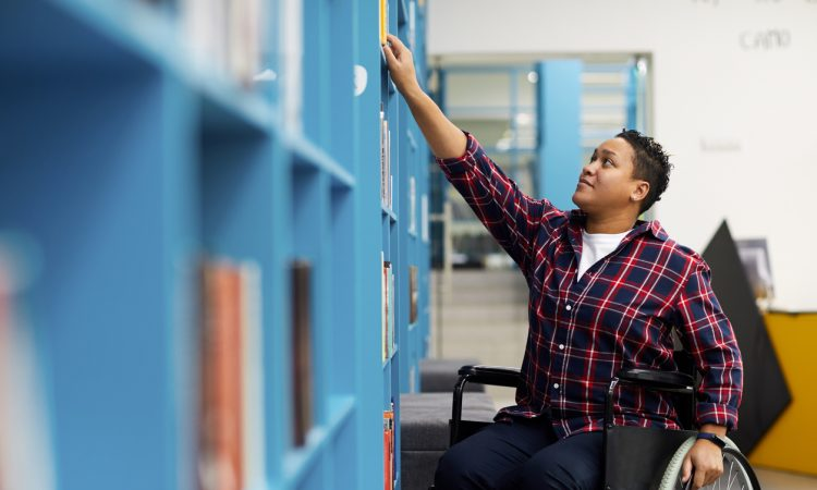 student in wheelchair choosing books while studying in college library