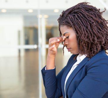 black businesswoman rubbing bridge of nose