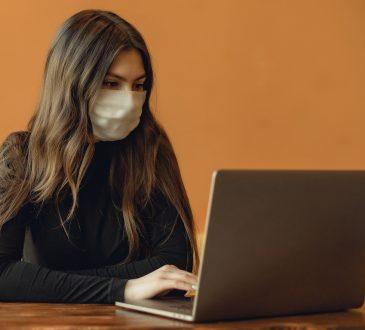 woman wearing mask typing on laptop