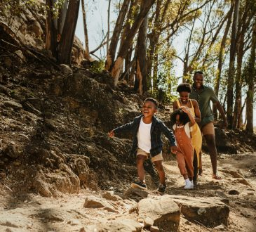 Young family running down rocky mountain trail.