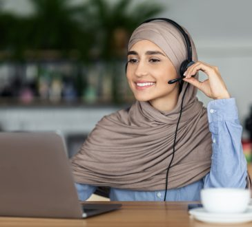 woman wearing headset and smiling at laptop screen
