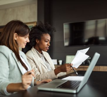 white woman and black woman working at table in office