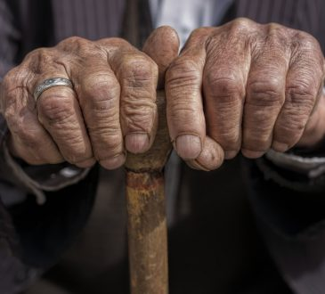 hand of a old man holding a cane