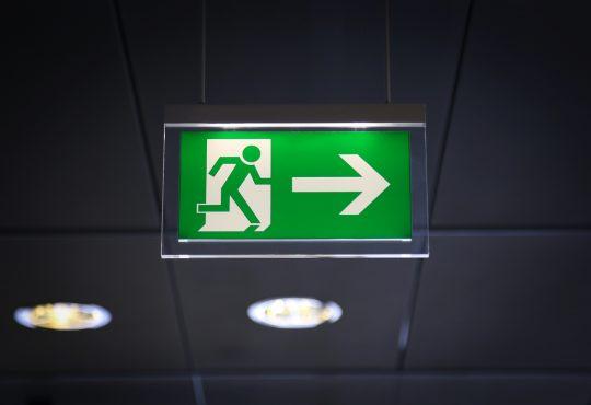 Emergency exit sign above a black doorway