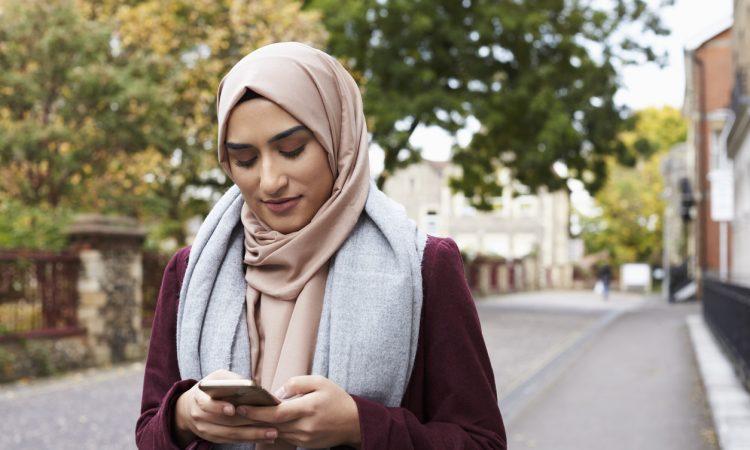 woman wearing hijab walking outside and texting