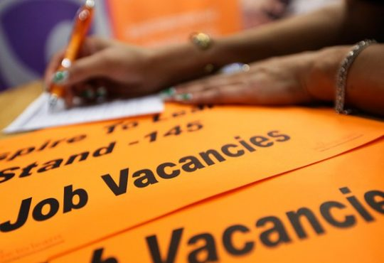 person writing on top of orange papers showing job vacancies
