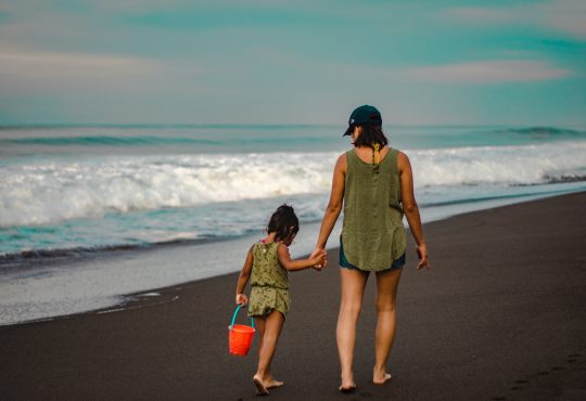 mom walking with daughter on beach away from camera