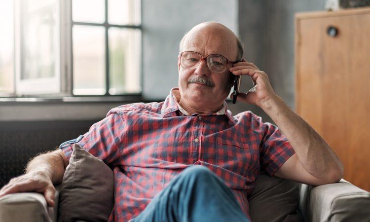 man talking on phone sitting at living room.