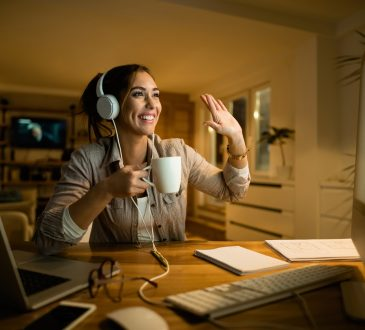Happy woman drinking tea and waving to someone while having video call over desktop PC in the evening at home.