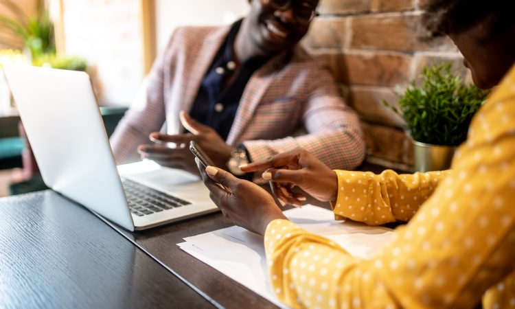 man and woman looking at laptop in cafe