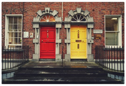 two differently coloured house front doors side by side