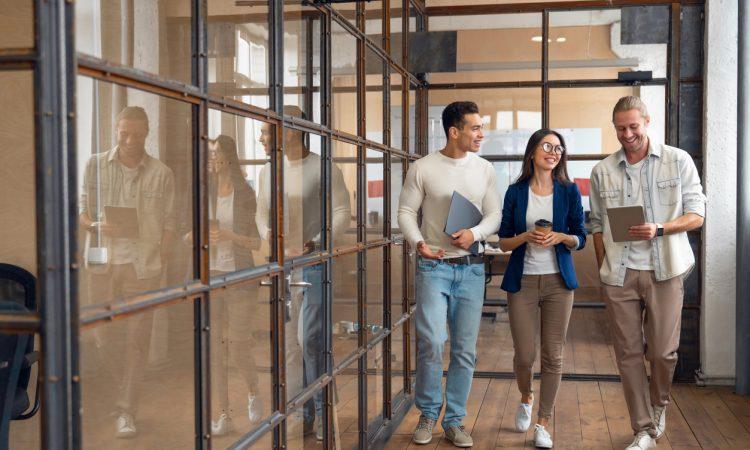 three colleagues walking in hallway of modern offic