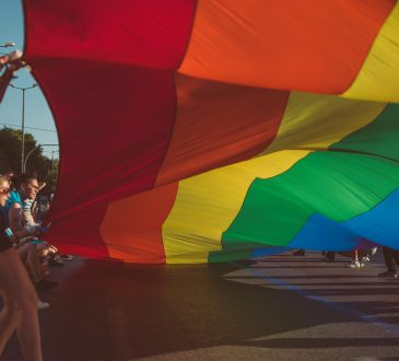 people holding edge of giant pride flag
