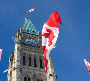 canadian flags flying in front of peace tower in ottawa