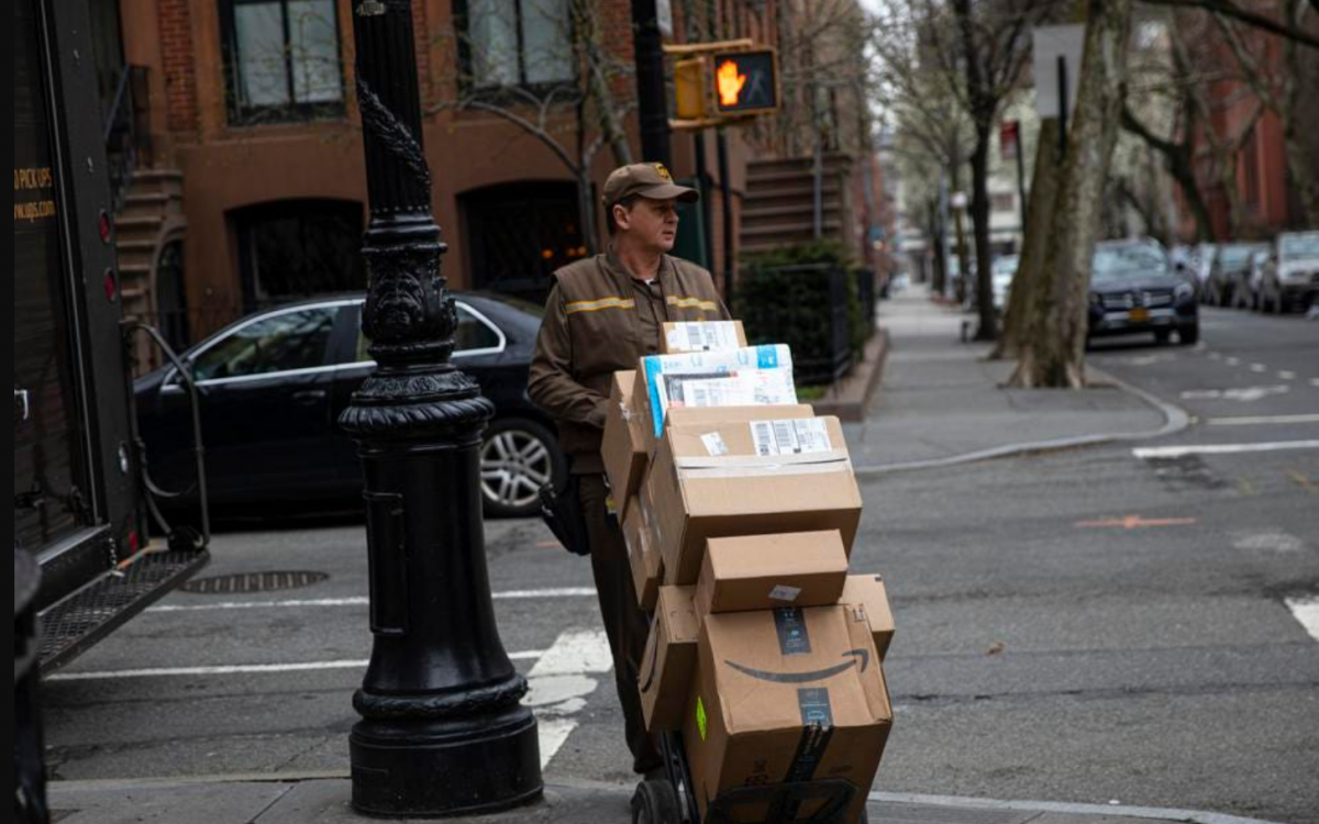 Middle aged delivery man in brown coveralls and hat, walking on the sidewalk of a small street with a trolly stacked with boxes for delivery