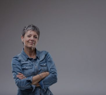 Confident senior woman with folded arms standing looking at camera with a thoughtful quiet smile over grey with copy space