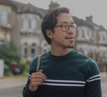 pensive male college student walking in residential area