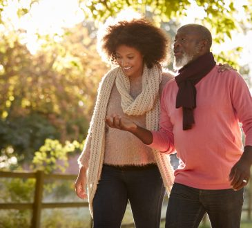 Senior Father With Adult Daughter on walk outside in fall