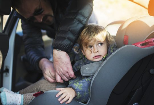 Young father putting baby girl in the car