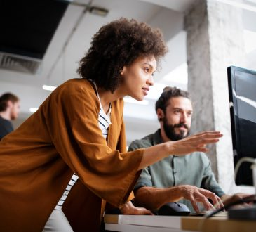 woman and man working together at computer in office
