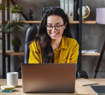 woman smiling and working on laptop in home office