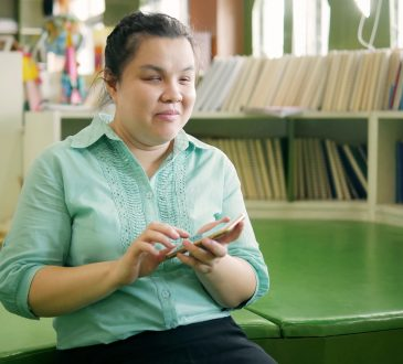 young blind woman using smart phone with voice accessibility