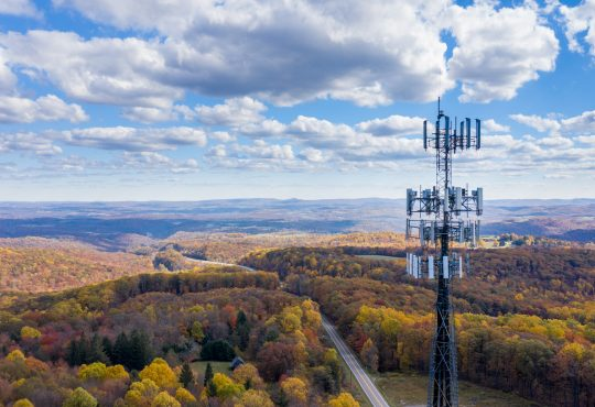 Aerial view of cell tower over forested rural area