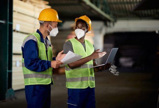 two men using laptop and communicating while working at lumberyard warehouse during COVID-19 pandemic.