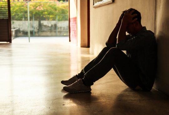 student sitting in school hallway with head in hands