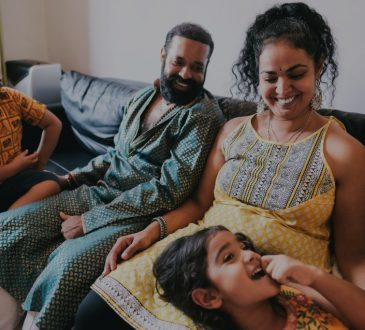 indian family laughing together on couch