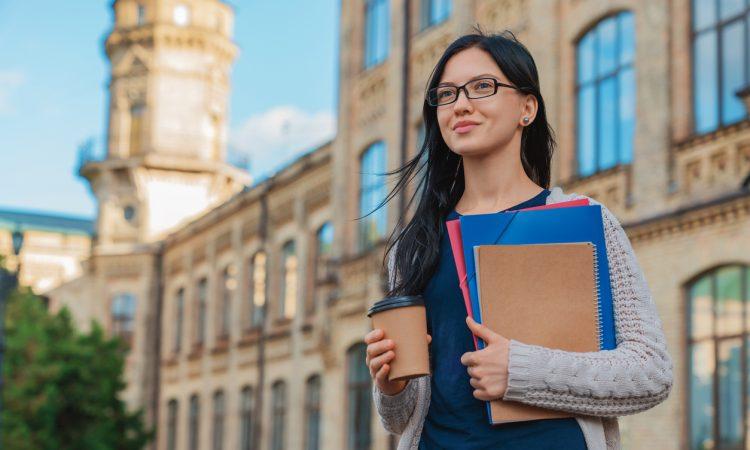 female student walking outside on university campus