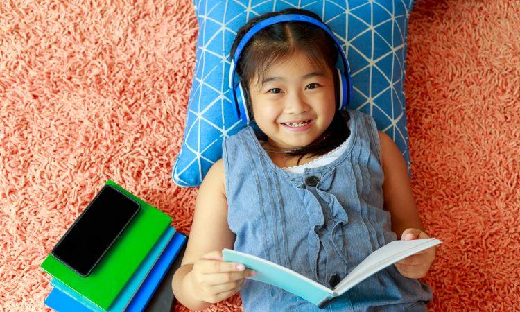 little girl lying on floor of bedroom reading and listening through headphones