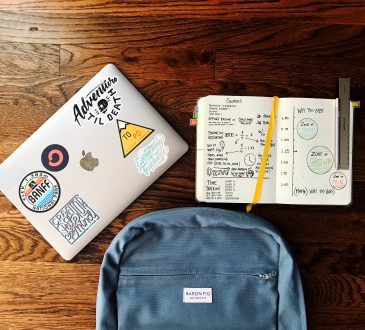 backpack, laptop and open notebook on table