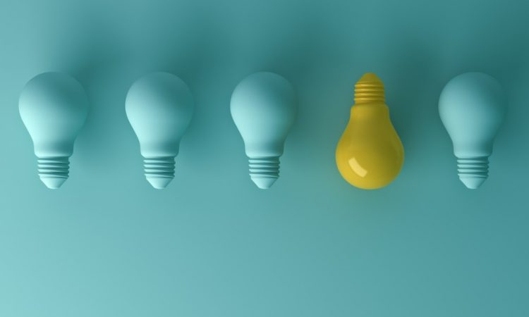blue lightbulbs in a row with one yellow one facing the other way
